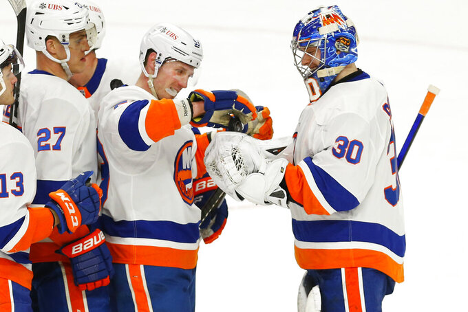 FILE - In this Feb. 16, 2021, file photo, New York Islanders forward Casey Cizikas (53) gives goalie Ilya Sorokin (30) the game puck to celebrate a 3-0 victory following the third period of an NHL hockey game against the Buffalo Sabres in Buffalo, N.Y.  The Islanders finalized most of their offseason work in one day by signing four players to multiyear contracts. Goaltender Ilya Sorokin got a three-year deal for $12 million, homegrown forward Anthony Beauvillier three years and $12.45 million, deadline pickup Kyle Palmieri $20 million over four years and fourth-line mainstay Casey Cizikas six years for $15 million. (AP Photo/Jeffrey T. Barnes, File)