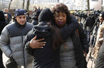 Gwen Carr, center right, mother of Eric Garner, is hugged by a woman, after a news conference outside of New York Police headquarters, Thursday, Dec. 6, 2018, in New York.   Daniel Pantaleo, a New York City police officer accused in the 2014 chokehold death of Garner, an unarmed black man,  will face a disciplinary trial in May. (AP Photo/Julio Cortez)