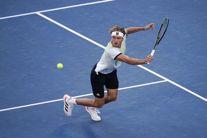 Alexander Zverev, of Germany, returns a shot to Karen Khachanov, of the Russian Olympic Committee, during the men's single gold medal match of the tennis competition at the 2020 Summer Olympics, Sunday, Aug. 1, 2021, in Tokyo, Japan. (AP Photo/Seth Wenig)