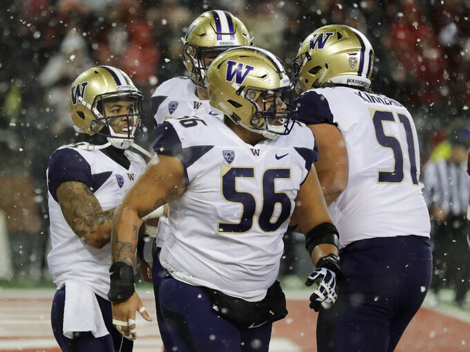 Washington running back Myles Gaskin, left, celebrates with teammates, including offensive lineman Nick Harris (56) after Gaskin scored a touchdown against Washington State during the first half of an NCAA college football game, Friday, Nov. 23, 2018, in Pullman, Wash. (AP Photo/Ted S. Warren)