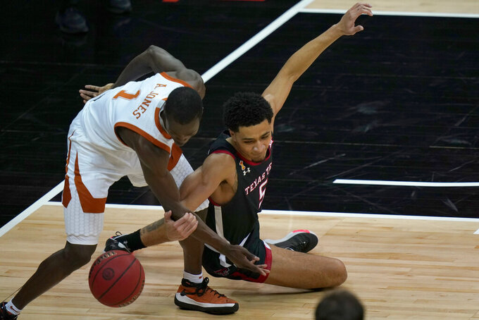 Texas guard Andrew Jones (1) and Texas Tech guard Micah Peavy (5) chase a loose ball during the first half of an NCAA college basketball game in the quarterfinal round of the Big 12 men's tournament in Kansas City, Mo., Thursday, March 11, 2021. (AP Photo/Orlin Wagner)