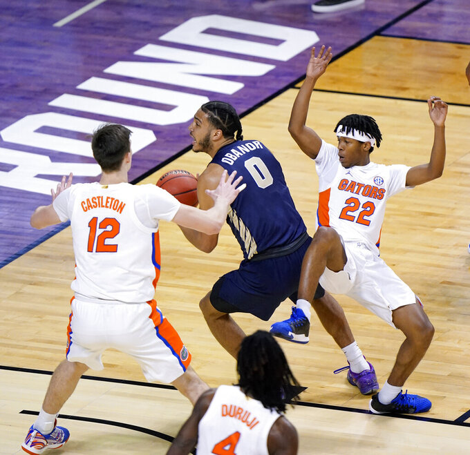Oral Roberts forward Kevin Obanor (0) drives to the basket between Florida forward Colin Castleton (12) and guard Tyree Appleby (22) during the first half of a college basketball game in the second round of the NCAA tournament at Indiana Farmers Coliseum, Sunday, March 21, 2021 in Indianapolis. (AP Photo/AJ Mast)