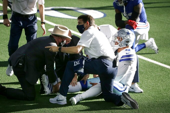 Dallas Cowboys quarterback Dak Prescott, right, is receives medical assistance from first responders and team medical personnel after Prescott suffered a lower right leg injury running the ball against the New York Giants in the second half of an NFL football game in Arlington, Texas, Sunday, Oct. 11, 2020. (AP Photo/Michael Ainsworth)
