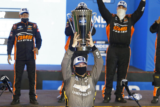 Sheldon Creed holds up the season championship trophy in victory lane after winning the NASCAR Truck Series auto race at Phoenix Raceway, Friday, Nov. 6, 2020, in Avondale, Ariz. (AP Photo/Ralph Freso)