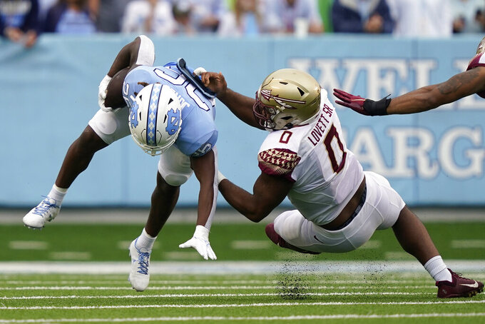 Florida State defensive tackle Fabien Lovett (0) tackles North Carolina running back D.J. Jones (26) during the first half of an NCAA college football game in Chapel Hill, N.C., Saturday, Oct. 9, 2021. (AP Photo/Gerry Broome)
