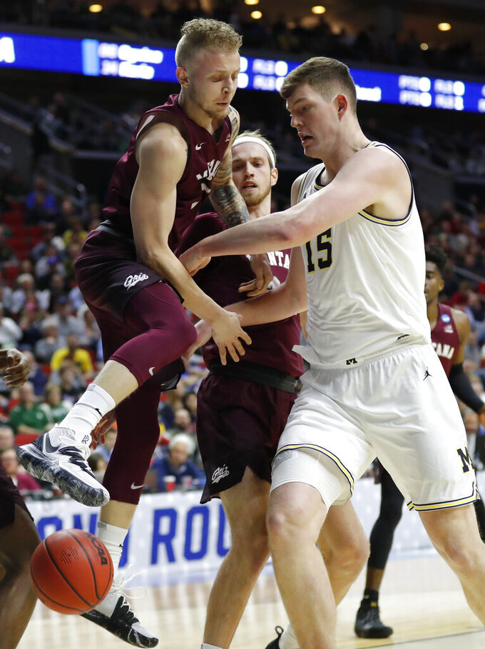 Montana guard Timmy Falls, left, fights for a loose ball with Michigan center Jon Teske during a first round men's college basketball game in the NCAA Tournament, Thursday, March 21, 2019, in Des Moines, Iowa. (AP Photo/Charlie Neibergall)