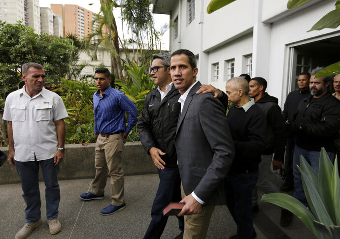 Venezuelan Congress President Juan Guaido, an opposition leader who has declared himself interim president, is surrounded by bodyguards a he leaves a meeting with leaders of public employee unions at the offices of an engineers' association in Caracas, Venezuela, Tuesday, March 5, 2019. Guaido said police officials were among those at the meeting with state workers who rely heavily on government subsidies to get by in a country suffering from hyperinflation and shortages of food and other necessities. (AP Photo/Fernando Llano)