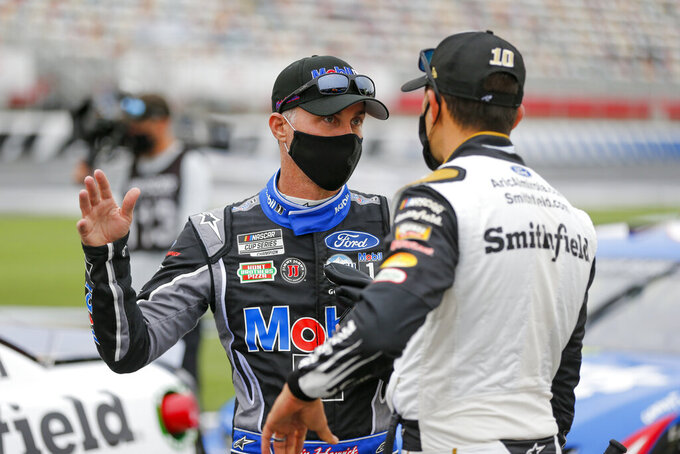 Kevin Harvick, left, talks to Aric Almirola before the start of a NASCAR Cup Series auto race at Charlotte Motor Speedway in Concord, N.C., Sunday, Oct. 11, 2020. (AP Photo/Nell Redmond)