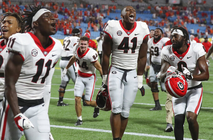 Georgia players celebrate a victory over Clemson in an NCAA college football game Saturday, Sept. 4, 2021, in Charlotte, N.C. (Curtis Compton/Atlanta Journal-Constitution via AP)