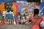 A woman takes photos of her daughters by a mural referencing the COVID-19 pandemic, painted in honor of health workers in Rio de Janeiro, Brazil, Thursday, May 21, 2020. The mural is by graffiti artist Angelo Campos, 39, who has lost two relatives to the new coronavirus. (AP Photo/Silvia Izquierdo)