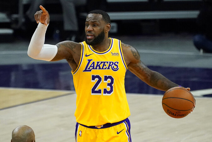 Los Angeles Lakers forward LeBron James (23) calls a play against the Phoenix Suns during the first half of a preseason NBA basketball game, Friday, Dec. 18, 2020, in Phoenix, Ariz. (AP Photo/Matt York)