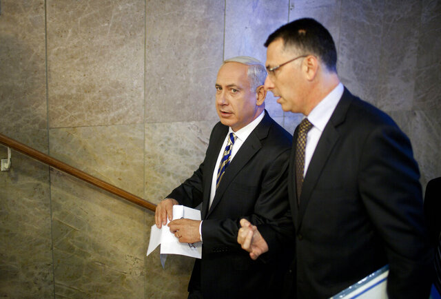 FILE - In this August 26, 2012 file photo, Israeli Prime Minister Benjamin Netanyahu, left, speaks to then Israeli Education Minister Gideon Saar as they arrive to the weekly cabinet meeting in Jerusalem. For years, Saar had been one of Netanyahu's most loyal and vocal supporters, serving as Cabinet secretary and government minister. Now the telegenic Saar, armed with near unrivaled political savvy and a searing grudge against his former boss, could prove to be Netanyahu's greatest challenge. (AP Photo/Uriel Sinai/Getty Images, Pool, File)