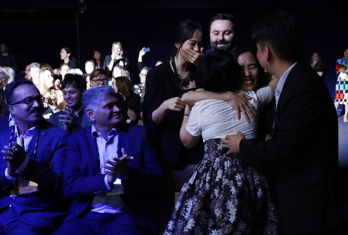 Members of Kitkit School embrace after winning the XPRIZE for Children's Literacy, Wednesday, May 15, 2019, in Los Angeles. (AP Photo/Marcio Jose Sanchez)