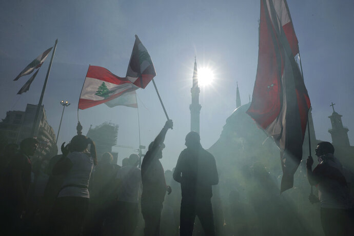Anti-government protesters wave Lebanese national flags as gather during separate civil parade at the Martyr square, in downtown Beirut, Lebanon, Friday, Nov. 22, 2019. Protesters gathered for alternative independence celebrations, converging by early afternoon on Martyrs' Square in central Beirut, which used to be the traditional location of the official parade. Protesters have occupied the area, closing it off to traffic since mid-October. (AP Photo/Hassan Ammar)