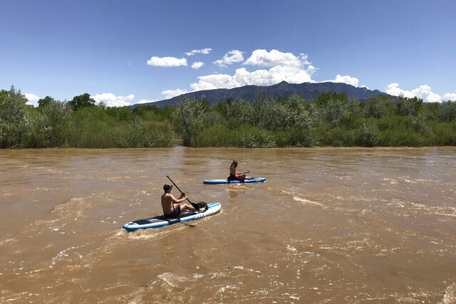 FILE - In this May 4, 2019, file photo, two kayakers float the Rio Grande through Corrales, New Mexico. New Mexico officials said Thursday, Jan. 23, 2020, the Trump administration's move to end federal protections for many of the nation's millions of miles of streams, arroyos and wetlands will be