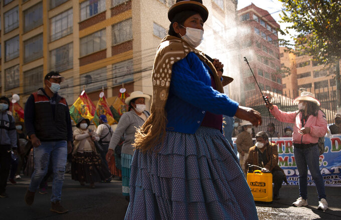 A woman sprays disinfectant on demonstrators amid the COVID-19 pandemic, during a march asking for free internet access and computers from the government, so that their children can take online classes, in La Paz, Bolivia, Monday, May 10, 2021. (AP Photo/Juan Karita)