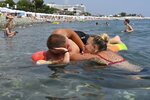 A couple enjoy the beach in the Black Sea resort of Sochi, Russia, Sunday, July 5, 2020. Tens of thousands of vacation-goers in Russia and Ukraine have descended on Black Sea beaches, paying little attention to safety measures despite levels of contagion still remaining high in both countries. (AP Photo/Artur Lebedev)