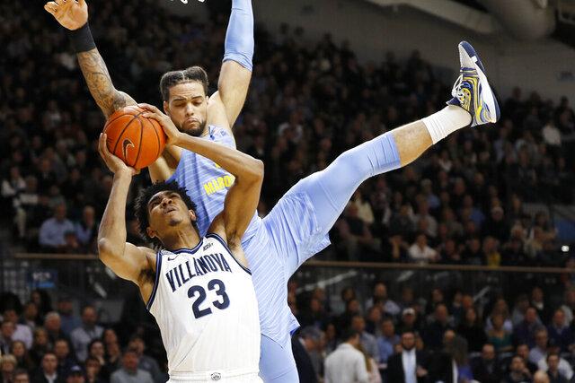 Villanova's Jermaine Samuels (23) tries to get a shot past Marquette's Theo John during the second half of an NCAA college basketball game Wednesday, Feb. 12, 2020, in Villanova, Pa. (AP Photo/Matt Slocum)