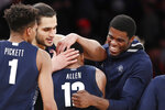 Teammates, including Georgetown guard Jamorko Prickett, left, and center Omer Yurtseven, second from left, grab Georgetown guard Terrell Allen (12) after Allen held onto the ball to preserve a one-point lead during the waning seconds of an NCAA college basketball game against St. John's, Sunday, Feb. 2, 2020, in New York. (AP Photo/Kathy Willens)