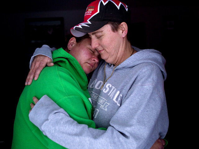 In this Feb. 13, 2020 photo, Christine Jackson, left, and Angela McDermitt-Jackson hold each other closely at their home in Montrose, Mich. The couple was married in Chicago in 2015. Their family is upset that daughter Destiney McDermitt was not allowed to write about gay marriage for a paper in school. (Jake May/The Flint Journal via AP)