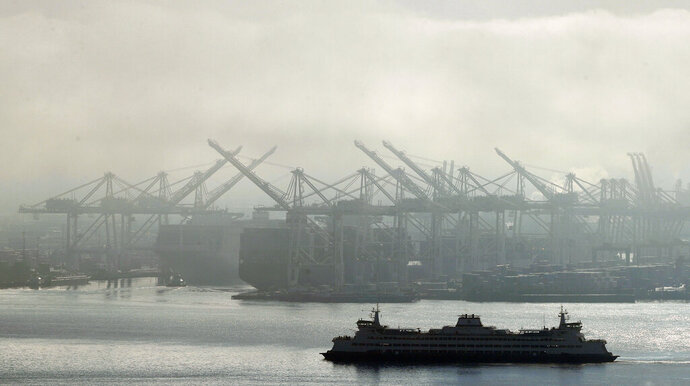 FILE - In this Dec. 31, 2018, photo a Washington state ferry sails on a foggy day near cranes at the Port of Seattle. On Friday, April 26, 2019, the Commerce Department issues the first estimate of how the U.S. economy performed in the January-March quarter. (AP Photo/Ted S. Warren, File)