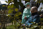 Palmiro Tami, 82, holds hand with his wife Franca Persico as the have a walk through the garden of the Fondazione Martino Zanchi nursing home, after receiving the second shot of Moderna COVID-19 Vaccine, in Alzano Lombardo, northern Italy, Monday, March 22, 2021. Italy's nursing homes have been declared an initial success in an otherwise lagging vaccine campaign. At a nursing home near Bergamo, one 82-year-old resident received his second jab, and a surprise visit from his 77-year-old wife. Their last hug had been through plastic on his birthday, in February. (AP Photo/Luca Bruno)