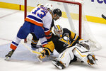 New York Islanders' Mathew Barzal (13) can't get his stick on a puck underneath Pittsburgh Penguins goaltender Matt Murray (30) with Justin Schultz, rear, defending during the overtime period of an NHL hockey game in Pittsburgh, Tuesday, Nov. 19, 2019. The Islanders won 5-4 in overtime. (AP Photo/Gene J. Puskar)