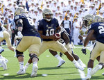 Navy quarterback Malcolm Perry takes a snap in the first quarter of an NCAA college football game against Holy Cross, Saturday, Aug. 31, 2019, in Annapolis, Md. (Paul W. Gillespie/Capital Gazette via AP)