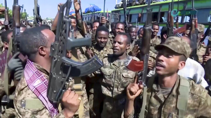 This image made from undated video released by the state-owned Ethiopian News Agency on Monday, Nov. 16, 2020 shows Ethiopian military cheering and dancing in front of cameras on a road in an area near the border of the Tigray and Amhara regions of Ethiopia. Ethiopia's prime minister Abiy Ahmed said in a social media post on Tuesday, Nov. 17, 2020 that