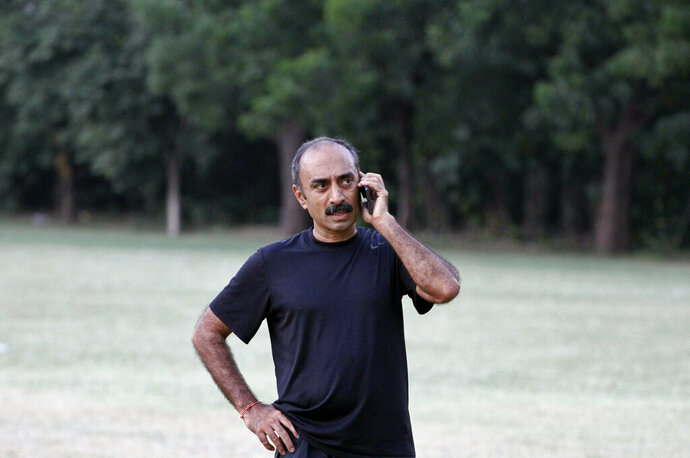 In this Sept. 9, 2015 file photo, Sanjiv Bhatt, an Indian officer with the intelligence bureau in the western state of Gujarat during the 2002 riots, speaks on his mobile phone in Ahmadabad, India. An Indian court has sentenced a former police officer, who alleged Prime Minister Narendra Modi's complicity in the killing of Muslims in western Gujarat state in 2002, to life in prison for a custodial death. Judge D.N. Vyas on Thursday, June 20, 2019, sentenced Bhatt in a case relating to the arrest of 150 people, one of whom died in police detention in 1990 in Gujarat state. The man's family said he died after he was tortured by Bhatt and some other police officers. (AP Photo/Ajit Solanki, File)
