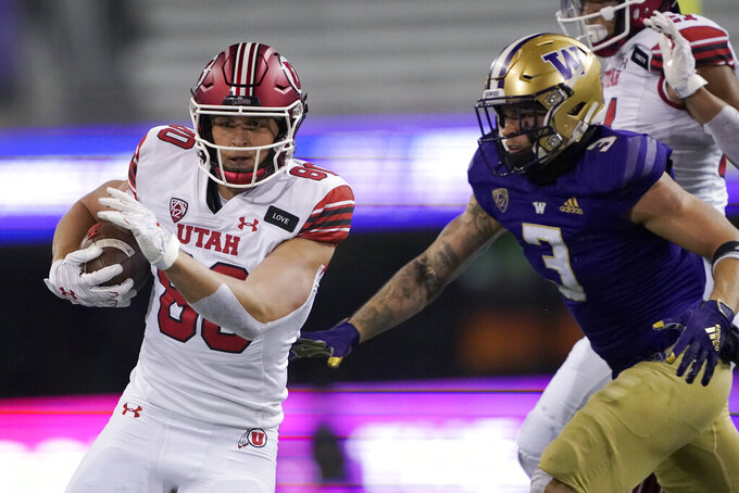 Utah tight end Brant Kuithe, left, runs the ball as Washington defensive back Elijah Molden (3) closes in during the first half of an NCAA college football game Saturday, Nov. 28, 2020, in Seattle. (AP Photo/Ted S. Warren)