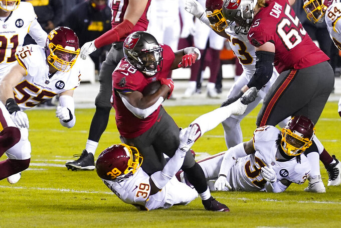 Tampa Bay Buccaneers running back Leonard Fournette (28) is taken down by Washington Football Team free safety Jeremy Reaves (39) during the first half of an NFL wild-card playoff football game, Saturday, Jan. 9, 2021, in Landover, Md. (AP Photo/Andrew Harnik)
