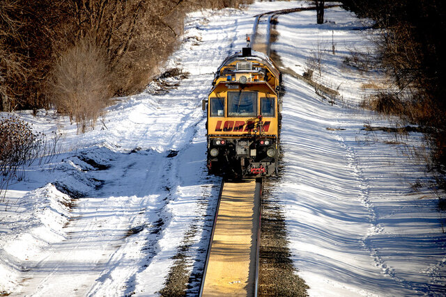 A train makes its way along a path where corn spilled from a train on a Canadian Pacific line and sat two inches deep for just under a half-mile, Tuesday, January 7, 2020 in Crystal, Minn. (Elizabeth Flores/Star Tribune via AP)