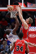 Chicago Bulls forward Lauri Markkanen (24) dunks against Charlotte Hornets center Bismack Biyombo (8) during the first half of an NBA basketball game Friday, Dec. 13, 2019, in Chicago. (AP Photo/Nam Y. Huh)