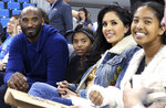 "FILE - In this Nov. 21, 2017, file photo, from left, Los Angeles Lakers legend Kobe Bryant, his daughter Gianna Maria-Onore Bryant, wife Vanessa and daughter Natalia Diamante Bryant are seen before an NCAA college women's basketball game between Connecticut and UCLA, in Los Angeles. Vanessa Bryant says she is focused on ""finding the light in darkness"" in an emotional story in People magazine. She details how she attempts to push forward after her husband, Kobe Bryant, and daughter Gigi died in a helicopter crash in early 2020. (AP Photo/Reed Saxon, File)"