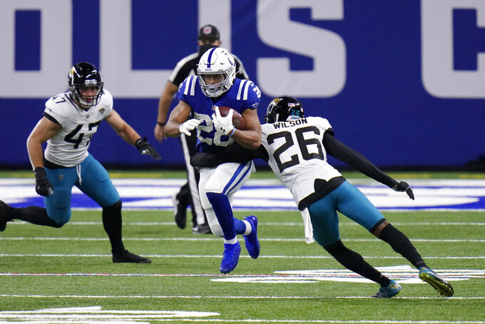 Indianapolis Colts' Jonathan Taylor (28) runs past Jacksonville Jaguars' Jarrod Wilson (26) during the first half of an NFL football game, Sunday, Jan. 3, 2021, in Indianapolis. (AP Photo/AJ Mast)