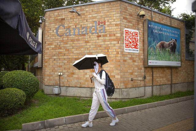 A woman wearing a face mask to help protect against the coronavirus walks past the Canadian Embassy in Beijing, Thursday, Aug. 6, 2020. China has sentenced a Canadian citizen to death on charges of manufacturing the drug ketamine amid heightened tension between the two countries. (AP Photo/Mark Schiefelbein)
