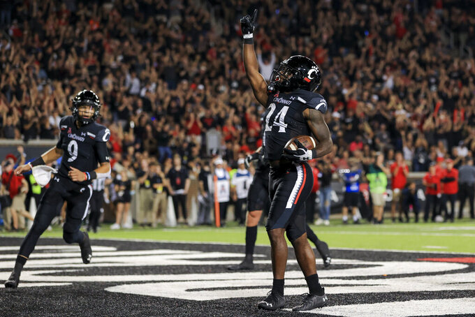 Cincinnati running back Jerome Ford (24) points skyward after scoring a touchdown during the first half of an NCAA college football game against Temple, Friday, Oct. 8, 2021, in Cincinnati. (AP Photo/Aaron Doster)