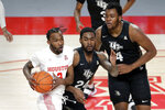Houston guard DeJon Jarreau, left, dishes off the ball under pressure from Central Florida guard Dre Fuller Jr. (24) and forward Jamille Reynolds (4) during the first half of an NCAA college basketball game Sunday, Jan. 17, 2021, in Houston. (AP Photo/Michael Wyke)