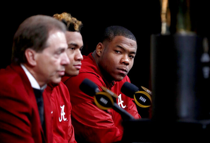 Alabama defensive lineman Da'Ron Payne, right, looks on during a press conference with quarterback Tua Tagovailoa, center, and head coach Nick Saban as the NCAA college football championship trophy is displayed in Atlanta, Tuesday, Jan. 9, 2018. Alabama beat Georgia 26-23 in overtime to win the NCAA college football playoff championship game on Monday night. (AP Photo/David Goldman)