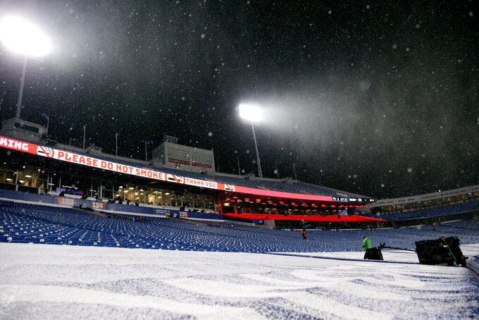 Workers walk through the stands as snow falls at Bills Stadium before an NFL divisional round football game between the Buffalo Bills and the Baltimore Ravens Saturday, Jan. 16, 2021, in Orchard Park, N.Y. (AP Photo/Jeffrey T. Barnes)