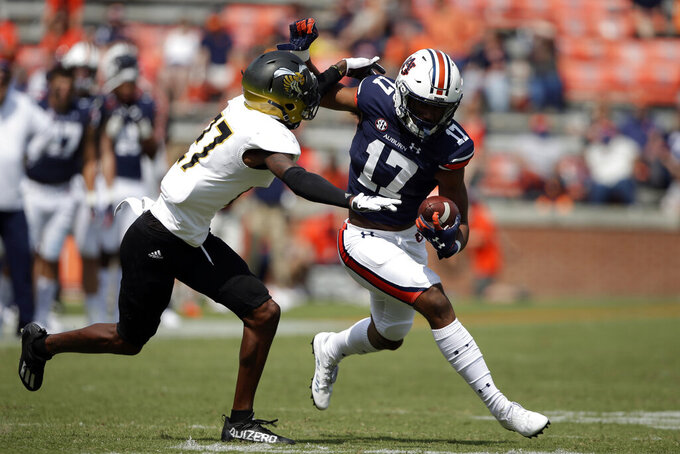 Auburn wide receiver Elijah Canion (17) tries to break free from Alabama State defensive back James Burgess (27) after a reception during the second half of an NCAA football game Saturday, Sept. 11, 2021, in Auburn, Ala. (AP Photo/Butch Dill)