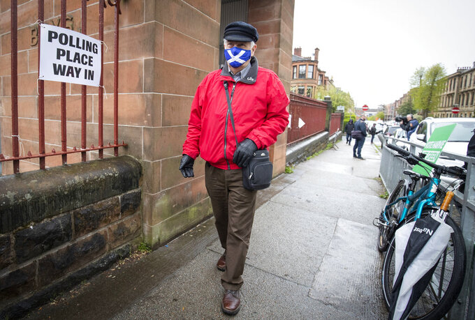 A man wearing a face mask arrives to vote at a polling station in Glasgow, Scotland, Thursday May 6, 2021. Scots are heading to the polls to elect the next Scottish Government - though the coronavirus pandemic means it could be more than 48 hours before all the results are counted. (Jane Barlow/PA via AP)