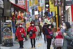 Tourist information helpers wearing face masks walk along a popular shopping street in Seoul, South Korea, Wednesday, Dec. 2, 2020. (AP Photo/Ahn Young-joon)