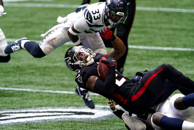 Atlanta Falcons running back Todd Gurley (21) is stopped by Seattle Seahawks strong safety Jamal Adams (33) during the first half of an NFL football game, Sunday, Sept. 13, 2020, in Atlanta. (AP Photo/John Bazemore)