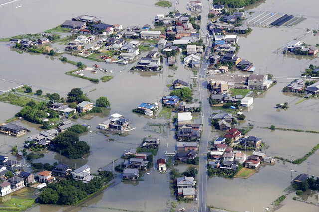This aerial photo shows the flooded area caused by the swollen Chikugo River, not seen in photo, in Kurume city, Fukuoka prefecture, southern Japan Wednesday, July 8, 2020. Pounding rain that already caused deadly floods in southern Japan was moving northeast Wednesday, battering large areas of Japan's main island, swelling more rivers, triggering mudslides and destroying houses and roads. (Kyodo News via AP)