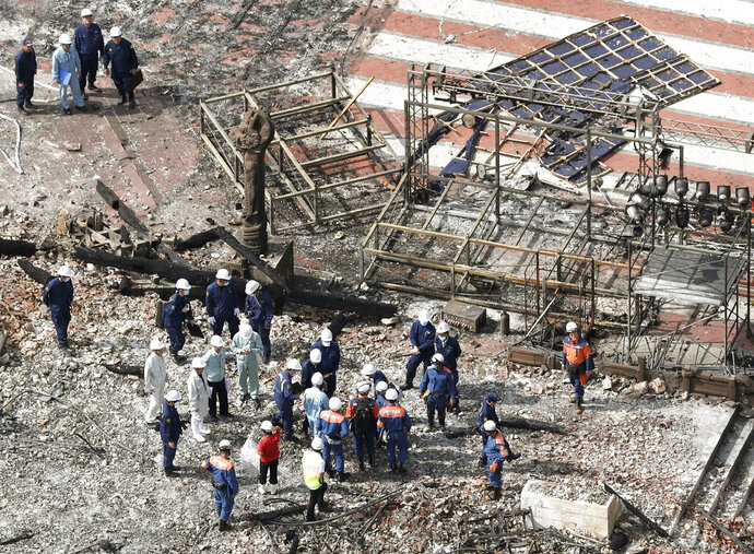 Investigators gather at the site of a fire on historic Shuri Castle in Naha, Okinawa, southern Japan Friday, Nov. 1, 2019. Fire and police investigators are inspecting the burned-out ruins of the castle to determine the cause of the fire that nearly destroyed the site that is a symbol of the Japanese island's cultural heritage and history of struggle. (Kyodo News via AP)