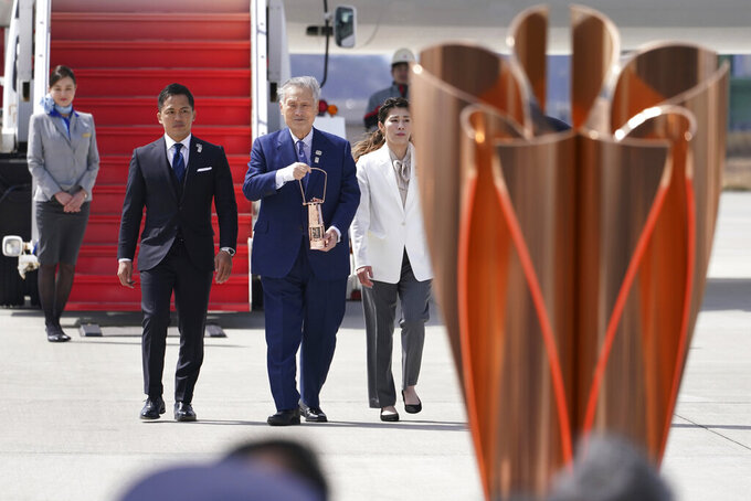 Tokyo 2020 Olympics chief Yoshiro Mori, center, followed by three-time Olympic gold medalists Tadahiro Nomura and Saori Yoshida, right, carries the Olympic flame during the Flame Arrival Ceremony at Japan Air Self-Defense Force Matsushima Base in Higashimatsushima in Miyagi Prefecture, north of Tokyo, Friday, March 20, 2020. The Olympic flame from Greece arrived in Japan even as the opening of the the Tokyo Games in four months is in doubt with more voices suggesting the games should to be postponed or canceled because of the worldwide virus pandemic. (AP Photo/Eugene Hoshiko)