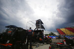 A pit crew works to dismantle their station as sort clouds roll in during the in the NASCAR Camping World Truck Series auto race at Watkins Glen International in Watkins Glen, N.Y., on Saturday, Aug. 7, 2021. The race was delayed due to a severe weather threat. (AP Photo/Joshua Bessex)