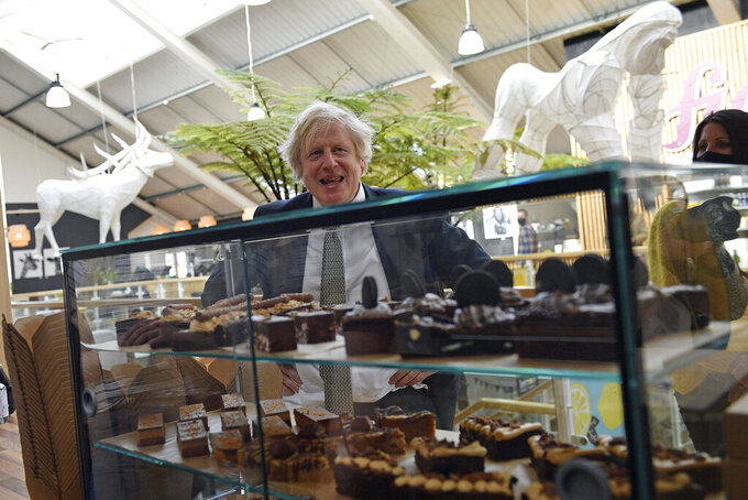 Britain's Prime Minister Boris Johnson looks at a display of cakes and desserts during a visit to Lemon Street Market in Truro, England, Wednesday, April 7, 2021  to see how they are preparing to reopen ahead of Step 2 of the roadmap on Monday. Johnson has confirmed that businesses from barbers to bookstores will be allowed to reopen next week and that Britain's slow but steady march out of a three-month lockdown remains on track. (Justin Tallis/Pool Photo via AP)